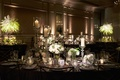 Reception in ballroom oval table velvet linen tall candleholders white flowers crystal votives