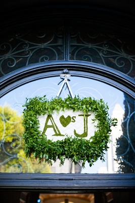 Leaf-framed white-tufted sign with moss letters