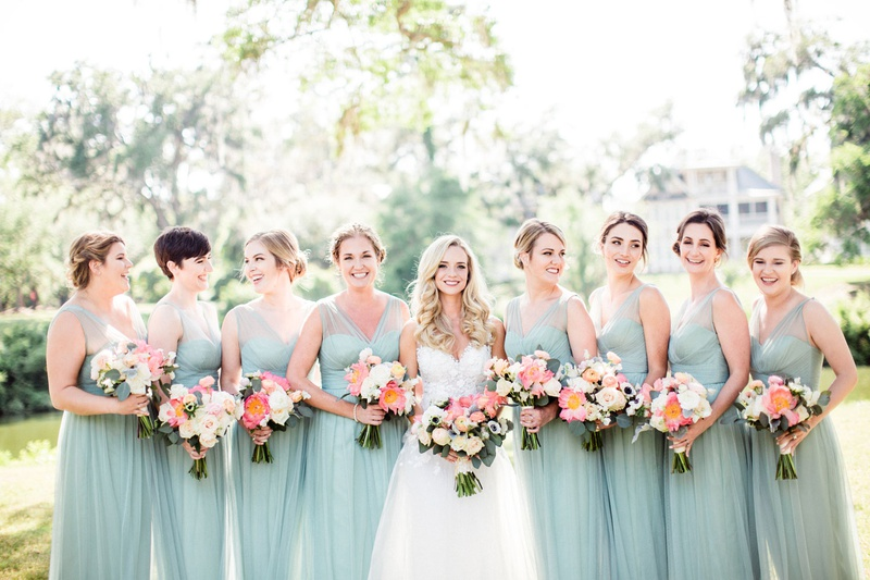 bride with bridesmaids in mint blue green dresses sheer necklines coral peony bouquets updos