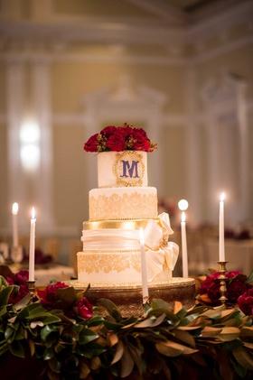 white cake red flowers purple monogram initial gold details candles ribbon renaissance wedding
