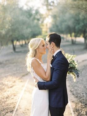 bride in pronovias wedding dress, groom in blue windowpane suit jacket almost kiss