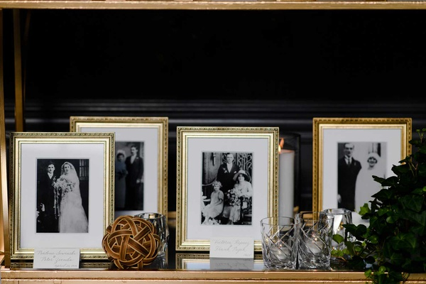 black and white family photos in gold frames white mat wedding reception family photo table