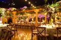 Wedding reception with wood pergola long table vineyard chairs flower print table linens centerpiece