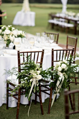 bride and groom reception chairs decorated with greenery and ivory roses