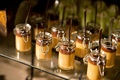 chocolate and caramel pudding in mini mason jars at wedding dessert table