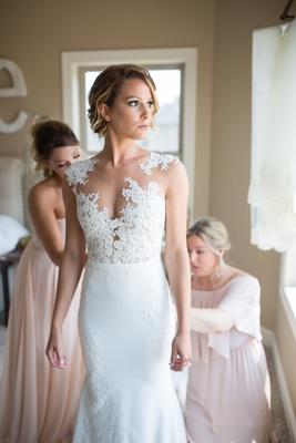 bride in pronovias gown with illusion neckline lace bodice, bridesmaids help bride into dress