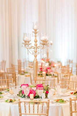 wedding reception round white table gold chairs pink flowers greenery gold candelabra salad course