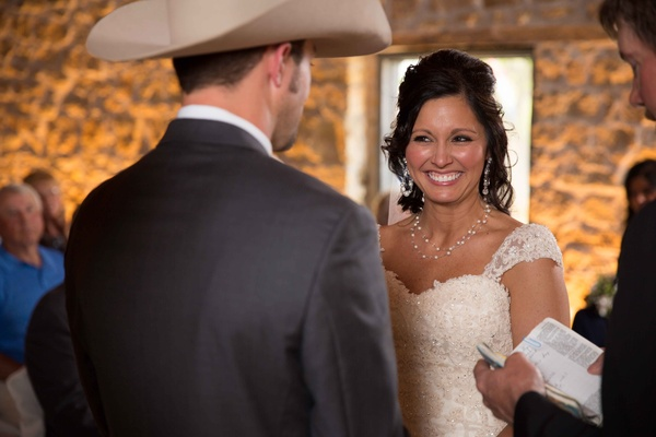 Bride at altar with cowboy groom smiling with pearl jewelry