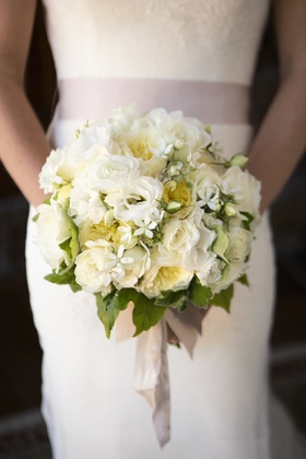 Bride in wedding dress holding roses and stephanotis