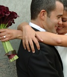 Bride hugs groom with burgundy calla lilies