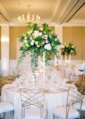 wedding reception light pink linens metallic chairs tall centerpiece with greenery white pink flower