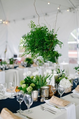 Nautical theme wedding reception with greenery centerpiece and low white tulip flower arrangements