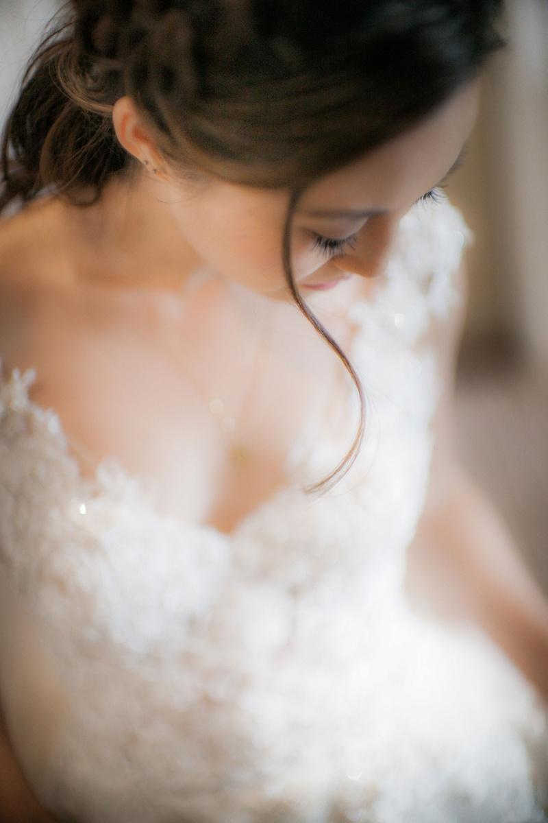 bride in elegant v neck lace wedding dress low pony tail curled wisp framing face