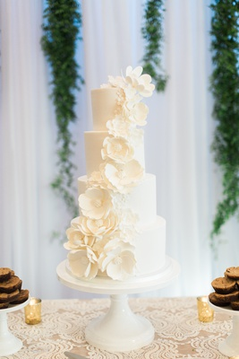 four tier white wedding cake with white sugar flowers
