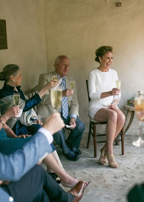 Bride in a short Mod dress with long sleeves, tan Jimmy Choo heels, laughs with guests