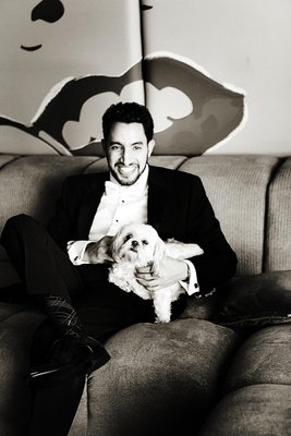 Black and white photo of groom on couch holding lap dog puppy