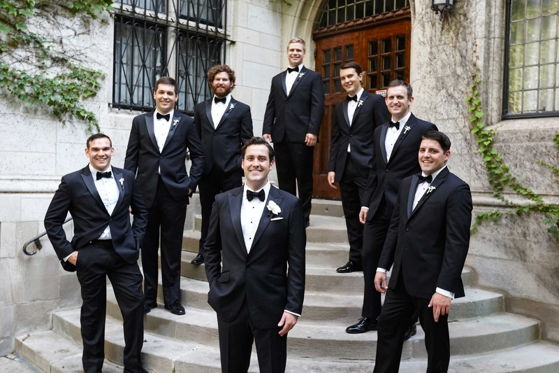 0a07bb829f6b Groom and groomsmen in tuxedo suits with black bow ties white pocket squares  boutonniere