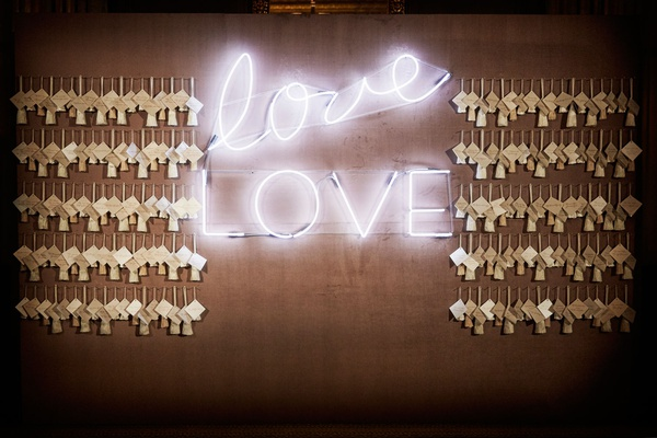 wedding reception escort card display on wall with love neon sign white light