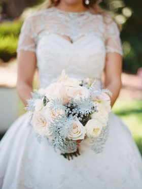 Bride holding wintry bouquet of verdure, berries, and roses in shades of white and pale pink