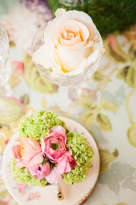 Pink and green flowers in gold-dipped tea cup and rose in glass