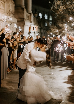 bride in wedding dress with fur wrap long hair headpiece guests with sparklers groom in white jacket