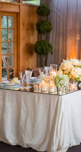 mirrored sweetheart table with glittery white linens and a mirror table, tufted loveseat