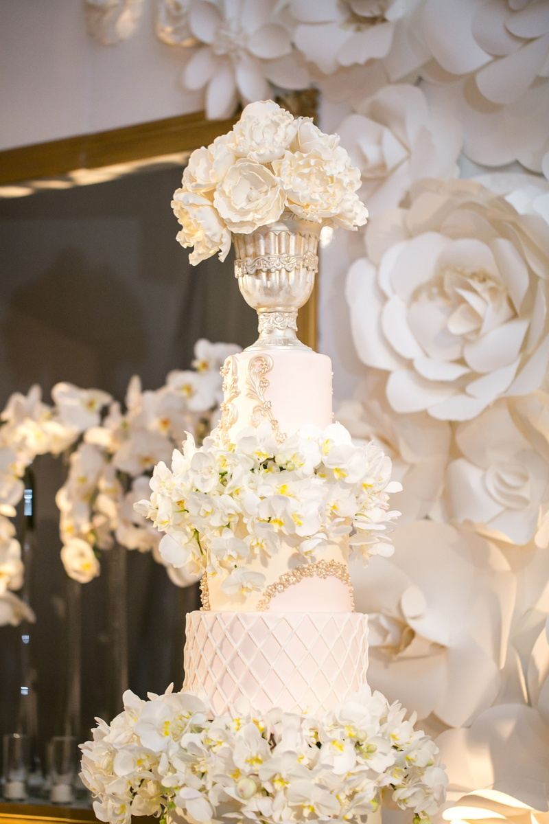 tall white wedding cake with orchids, chalice on top tier