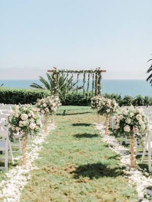 wedding ceremony grass lawn pink white flowers wood arbor greenery pink flowers