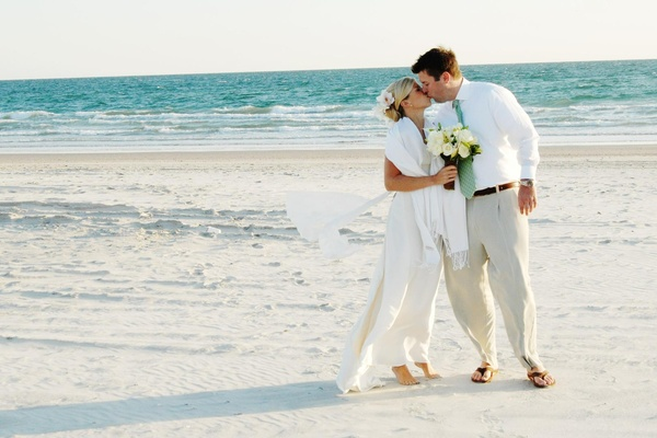 Bride and groom kiss on sand at beach wedding