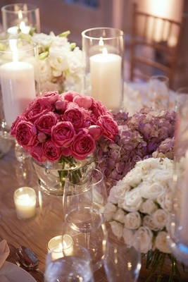 Pillar candles in hurricane vases separate arrangement of pink purple and white centerpiece design