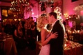 Bride and groom kiss in front of wedding guests