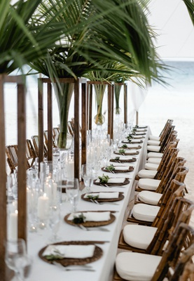 wedding reception long white table palm tree centerpiece wood bamboo chairs ocean bahamas