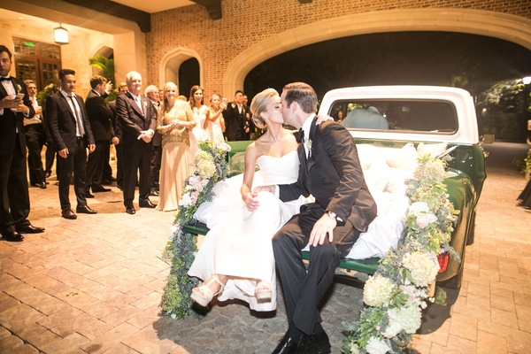 Bride and groom kiss and leave sitting on a truck
