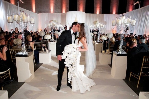 Chad Carroll kisses Jennifer Stone at wedding ceremony bride wears Oscar de la Renta orchid bouquet