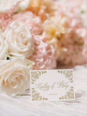 Wedding reception table with Ceci New York place card with gold damask print, white roses