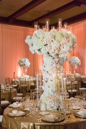 Flower sculpture centerpiece with candelabra details gold linens tall flower arrangement