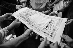 Black and white photo of ketubah family holding paper laser cut design details