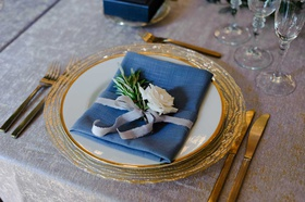 wedding reception place setting gold plate china blue napkin white rose rosemary herb sprig ribbon