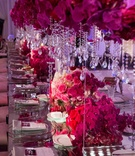 Long reception table with pink orchid and rose flowers crystal strands suspended from flowers