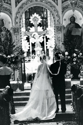 Black and white photo of bride and groom wearing wedding crowns