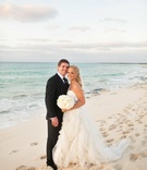 Bride and groom stand in sand in front of ocean