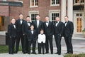 Groomsmen in black tuxes with bow ties, ring bearer in white tuxedo jacket with black bow tie
