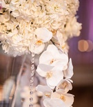 White flower arrangement at reception with orchid and crystal strands