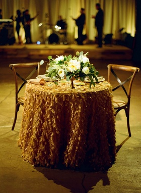 Sweetheart table with ruffle linen tablecloth with green and white low centerpiece wooden chairs