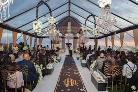Wedding ceremony resort at pelican hill clear tent black gold aisle runner white flower chandeliers