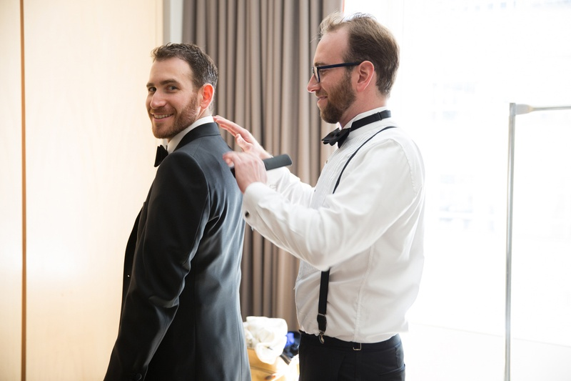 a groomsman helps the groom put on his suit jacket before the ceremony