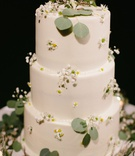 three layer wedding cake vegan with fresh greenery and flowers white with yellow centers