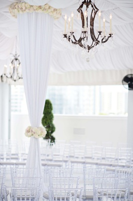 Faux-candlelit light fixture above clear chairs