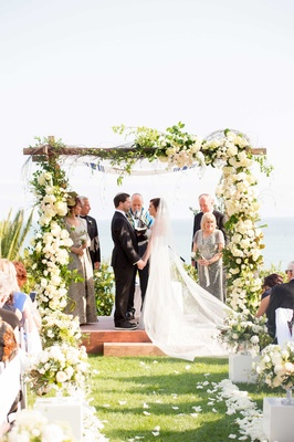 couple exchanges vows under wooden chuppah cathedral veil black tuxedo jewish wedding white flowers