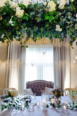 wedding reception head table low centerpiece candle overhead greenery overhead white roses settee